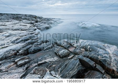 Tranquil Minimalist Landscape Of Stony Coast And Calm Water