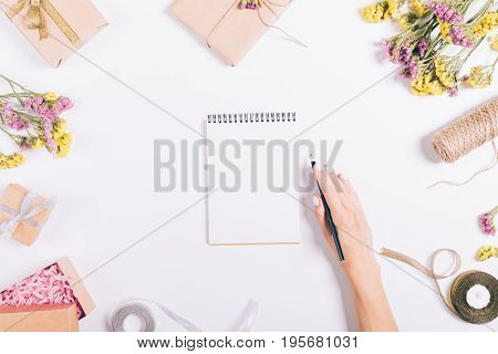 Female Hand Writing In A Paper Notebook On A White Table With Decorations