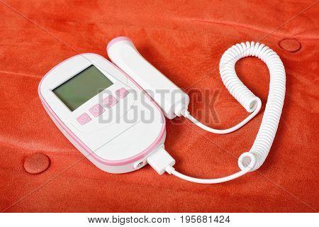 Medicine - Fetal Doppler on a red textile background