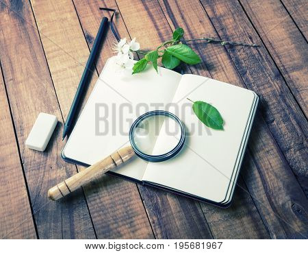 Still life with blank notebook magnifier flowers and green leaves on old wooden table background. Responsive design template.
