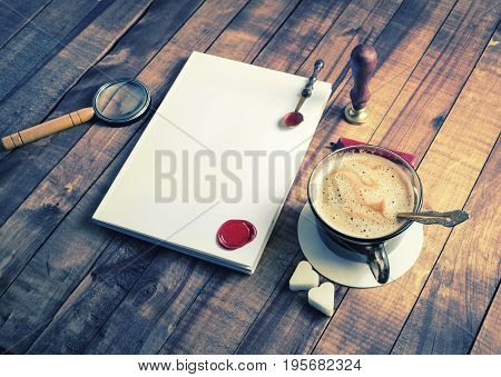 Vintage still life with stationery and coffee cup on wood background. Mockup for placing your design. Responsive design template.