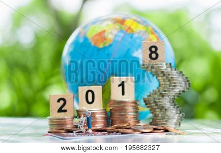 Tiny miniature shoppers model with shopping cart on a pile of coins and credit card or debit card with a wooden numbers 2018 on growing stacks of coins and globe background using as E-commerce online business background concept.