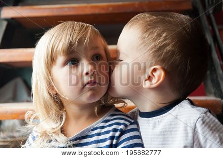 Little boy kisses the girl on the cheek. First kiss