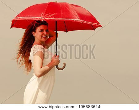 Beauty of ginger hair concept. Portrait of beautiful happy redhead adult plus size woman holding red umbrella.