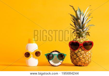 Pineapple, coconut and sunblock wearing sunglasses on a bright yellow background