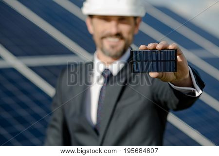 Close up view on photovoltaic element in hand of busines client. Man at solar station holding detail of solar panel.