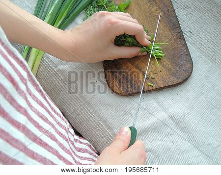 Female hands chopping herbs on the old chopping board, vintage linen tablecloth