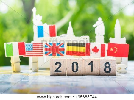 A wooden number 2018 with internation flags background on a world map using as happy new year 2018 concept international cooperationteamwork and partnership business concept.