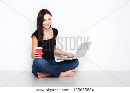 Freelance work with laptop. Blogging female. Smiling freelancer girl surf internet at white studio background with crossed legs and coffee cup