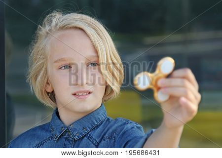 Blond school aged girl playing with a gold fidget spinner. A popular trendy toy.