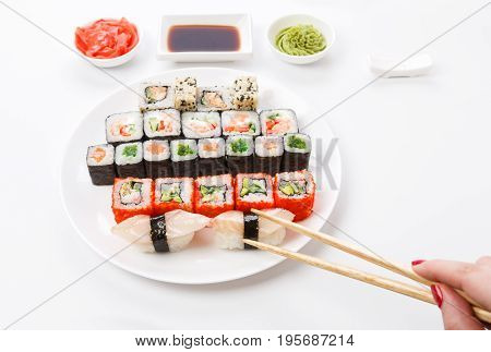 Japanese food restaurant. Sushi set served on white platter with soy sauce, ginger and wasabi. Female hand with chopsticks picking one piece. Pov at white background with copy space