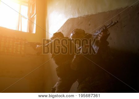 Photo of airsoft players with weapons in camouflage at building,