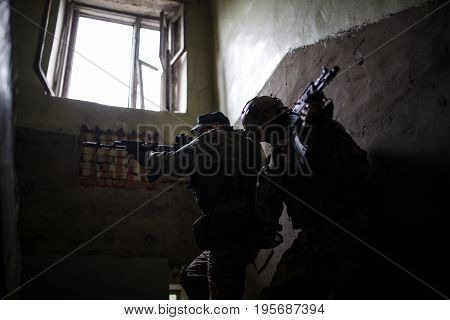 Photo of soldiers with weapons in camouflage on task in building