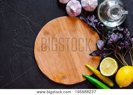 Mockup for menu. Cutting board and vegetables on black background top view.