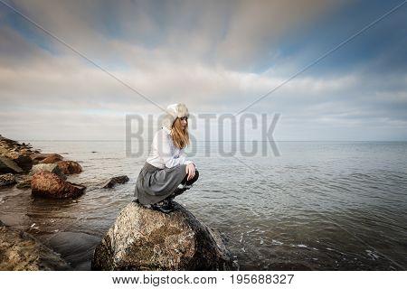 Woman On Stones Near Sea