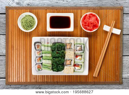 Japanese food restaurant delivery - sushi maki, unagi and roll platter set on mat on gray wood background, above view