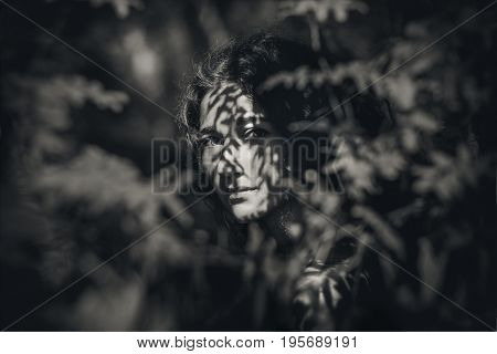 beautiful young woman in forest with shades on her face