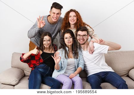 Happy students friends having fun, taking selfie and posing to camera, sitting on couch indoors