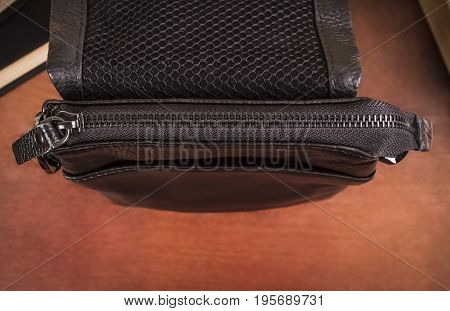 Men's bag with closed zipper close-up on a brown background