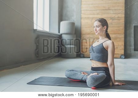 Attractive girl practicing yoga sitting in padmasana. Young woman in lotus pose doing relaxation exercise on mat at sport club interior, copy space