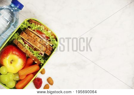 Green school lunch box with sandwich, apple, grape, carrot and bottle of water close up on white wooden  background. Healthy eating habits concept. Flat lay composition (from above, top view).