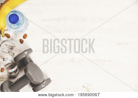 Fitness concept with dumbbells, water, measuring tape and fresh fruits on white wooden background