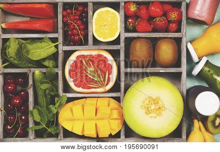 Fresh juices or smoothies with fruits and vegetables in wooden tray on blue background, top view, selective focus. Detox, dieting, clean eating, vegetarian, vegan, fitness, healthy lifestyle concept