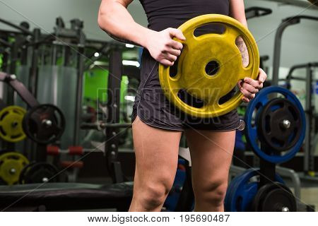 Young healthy man with big muscles holding disk weights in gym. Fitness, sport, training, motivation and lifestyle concept.