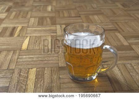 Mug of fresh beer with cap of foam on wooden background.