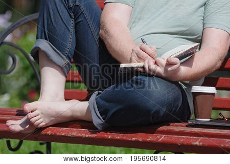 Man Sitting On The Bench At The Park Writing In His Notebook Working Inspiring