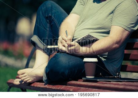 Man Writing In His Notebook In Park