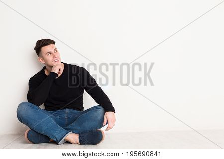 Smiling young man looks up, sitting on the floor at white background, copy space