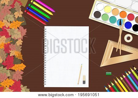 School supplies and a blank notepad ready for your text are lying on a brown wooden table. The edge forms colorful autumn leaves.