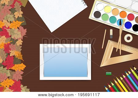 School supplies and a tablet with empty screen ready for your text are lying on a brown wooden table. The edge forms colorful autumn leaves.