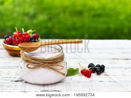 Yogurt in a jar and a saucer with white wooden berries on a table in the fresh air