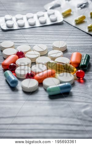 Vitamins and supplements. Pills and pill bottle on grey wooden table background.