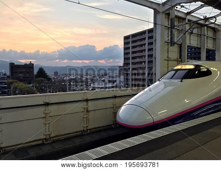 FUKUSHIMA JAPAN - APRIL 21 2017: High-speed train is at the platform of the railway station of Fukushima on backgroubd of the sunset