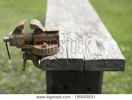 Abandoned rusty clamp attached to a wooden bench. Outdoor cropped shot
