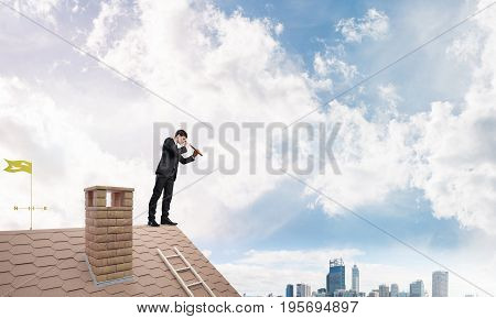 Young determined businessman standing on house roof and looking in spyglass. Mixed media