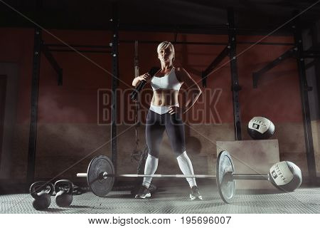 Beautiful sports blonde standing with ropes in the gym. Fitness woman in the gim.