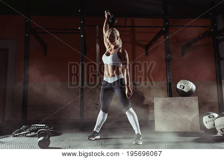 Fitness woman doing a weight training by lifting kettlebell. Muscular fitness woman, holds up a black kettlebell in the gym. Fitness woman in the gym. Fitness woman.