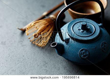 An arrangement of a cast iron tea pot and tea whisk