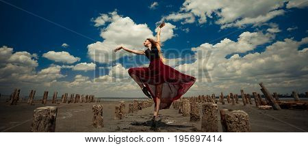 Ballerina in transparent dress is dancing in sand on beach and picturesque sky background, next there are wooden columns.