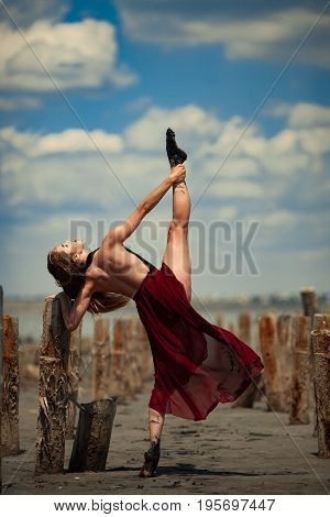 Ballerina in transparent dress is dancing on beach and picturesque sky background, next there are wooden columns.
