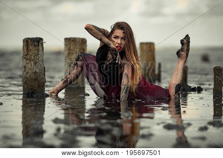 Young muddy woman in red dress is dancing in water on mud estuary, next there are wooden columns.