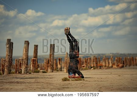 Young man smeared with therapeutic mud and stands on head on beach background. Next there are wooden columns. Spa.