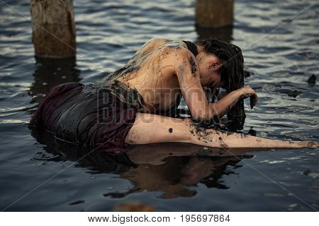 Young woman bathing in therapeutic water of mud estuary, next there are wooden columns. Spa.