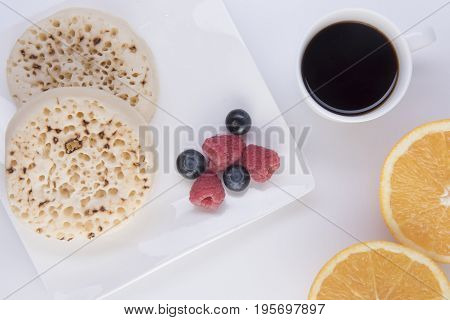 Crumpet with fruit on a white plate with black coffee and an orange cut in half