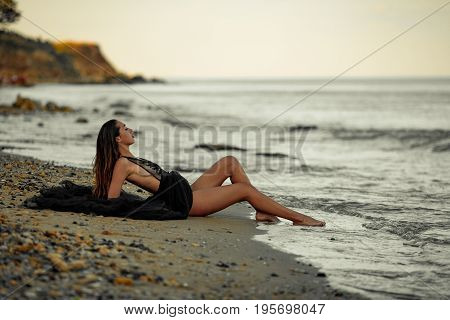 Young woman in long black dress sits on sand beach by the sea. Waves wash her feet.