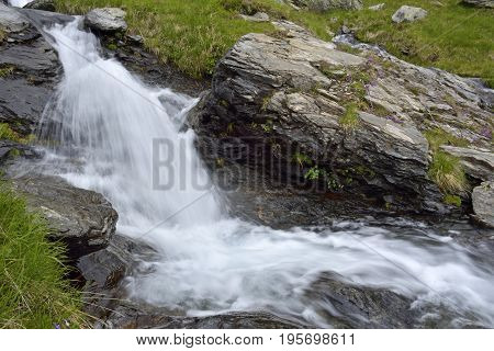 Deep forest waterfall. Mountain river with rapids and waterfalls. Carpathian.